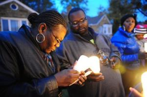 Charles Hannah lights Theresa Walker's candle, left,  at a candlelight vigil for Renisha McBride in front of the home where she was shot in Dearborn Heights, Mich.