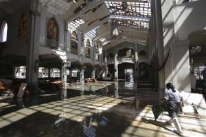 A Filipino typhoon survivor walks inside the damaged Santo Nino church in Tacloban city, Leyte province, central Philippines.