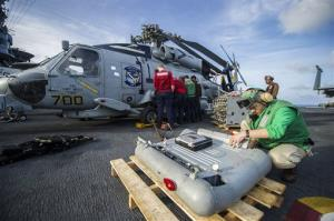 Sailors  remove equipment from a  helicopter  aboard the aircraft carrier USS George Washington to make room for transport of cargo and personnel.