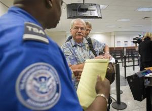 A passenger is briefed by a TSA trainer before going through a new expedited security line Tuesday, Oct. 4, 2011 in Atlanta.