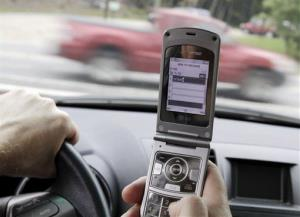 In this Sept. 20, 2011 file photo, a phone is held in a car in Brunswick, Maine.