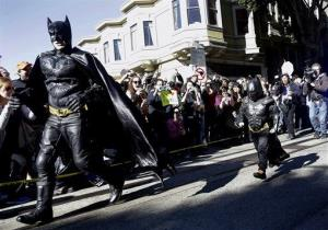 Miles Scott, dressed as Batkid, right, runs with Batman after saving a damsel in distress in San Francisco Friday.