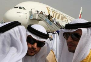 Emirati officials greet each other in front of an Emirates Airbus A380 during the opening day of the Dubai Airshow in Dubai, UAE, Sunday, Nov. 17, 2013.