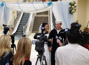 In this photo courtesy of Heidi Jared, Navy seaman Dylan Ruffer and wife Madison, both from Chester, Calif., talk to reporters after getting married at the Reno-Tahoe International Airport.