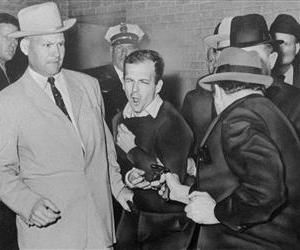 In this Nov. 24, 1963 file photo, Lee Harvey Oswald reacts as Dallas night club owner Jack Ruby, foreground, shoots at him from point blank range in a corridor of Dallas police headquarters.