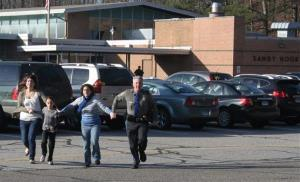 In this Friday, Dec. 14, 2012 photo a police officer leads two women and a child from Sandy Hook Elementary School in Newtown, Conn.
