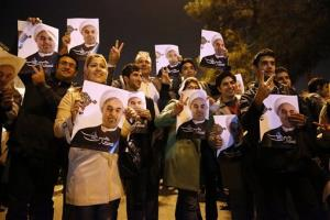 Iranians hold posters of President Hassan Rouhani as they welcome Iranian nuclear negotiators back from Geneva last night.