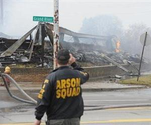 An arson investigator photographs flames and smoke from the Park Medical Plaza office building in Detroit on Tuesday, April 9, 2013.