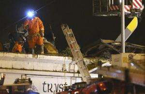 Firefighters and rescue workers inspect the damage on the roof of the building at the site of a helicopter crash, in Glasgow early Saturday Nov. 30, 2013.
