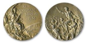 This handout provided by SCP Auctions, Inc., shows the front, left, and back, right, of one of Jesse Owens' four gold medals won at the 1936 Olympics in Berlin.