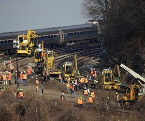A train passes by the scene of repair efforts at the site of a train derailment in the Bronx borough of New York, Dec. 3, 2013.