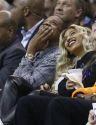Jay Z, left, and Beyonce look up at the scoreboard during an NBA basketball game between the Oklahoma City Thunder and the Los Angeles Clippers in Oklahoma City, Thursday, Nov. 21, 2013.