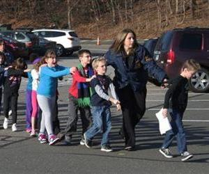 Connecticut State Police lead a line of children from the Sandy Hook Elementary School in Newtown, Conn. on Friday, Dec. 14, 2012.