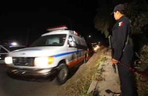A police agent stands guard as an ambulance leaves the village of Hueypoxtla, Mexico, Wednesday, Dec. 4, 2013.