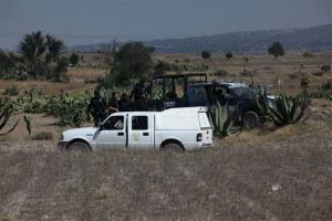 Men stand next to National Commission of Nuclear Safety and Mexican Federal Police vehicles in a field near the village of Hueypoxtla, Mexico, Thursday, Dec. 5, 2013.