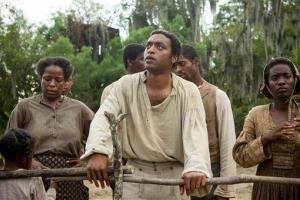 This image released by Fox Searchlight shows Chiwetel Ejiofor, center, in a scene from 12 Years A Slave.