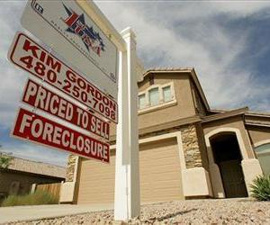 In this Sept. 26, 2007 file photo, a realty sign stands in front of one of the many homes that are in foreclosure in the Villages of Queen Creek in Queen Creek, Ariz.