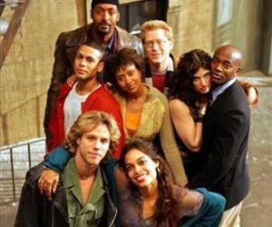 The cast of the film Rent (Adam Pascal, Rosario Dawson, Wilson Jermaine Heredia, Tracie Thoms, Idina Menzel, Taye Diggs, Jesse Martin, Anthony Rapp) pose on a film set in San Francisco on May 25, 2005.