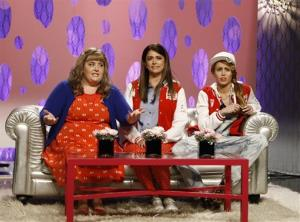 This Oct. 5, 2013 photo shows from left, Aidy Bryant, Cecily Strong, and guest host Miley Cyrus in a scene from the late-night comedy series Saturday Night Live.