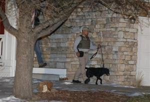 Police use a dog to do an initial search at the Highlands Ranch, Colo., home of the 18-year-old shooting suspect Karl Pierson.