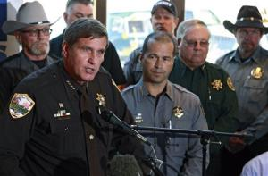 In this May 17, 2013 file photo, Weld County, Colo., Sheriff John Cooke, left, with other sheriffs standing behind him, speaks during a news conference on the lawsuit.
