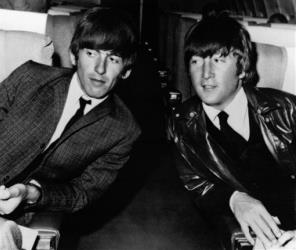 In this May 25, 1964 file photo, Beatles George Harrison, left, and John Lennon, are seen aboard an airplane in Los Angeles before leaving for London.