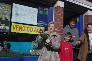 """The owner of a lottery office Maria Luisa Ron holds a wine bottle as she celebrates with family and friends after selling the first Christmas lottery prize """"El Gordo"""" in Leganes, Spain, Sunday, Dec. 22, 2013."""