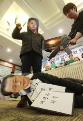 College students wearing masks of North Korean leader Kim Jong Un, top, and his uncle Jang Song Thaek perform during a press conference denouncing Kim's dictatorship.