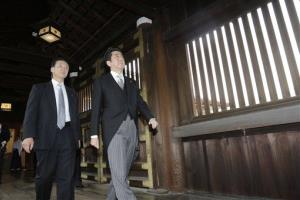 Japanese Prime Minister Shinzo Abe, followed by a security police officer, walks at Yasukuni Shrine to pay respect to the war dead, in Tokyo Thursday, Dec. 26, 2013.