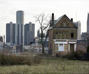 In a photo from Monday, Dec. 2, 2013, an empty field in Brush Park, north of Detroit's downtown is shown with an abandoned home.