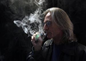 John Hartigan, proprietor of Vapeology LA, a store selling electronic cigarettes and related items, takes a puff of an electronic cigarette at his store in Los Angeles.