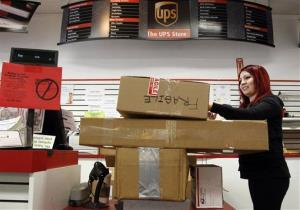 In this Jan. 30, 2012 photo, UPS Store employee Candy Mojica weighs packages before shipping them.