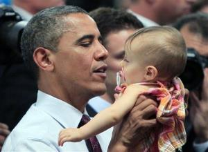 President Obama holds a baby after a town meeting in Cincinnati in 2012.