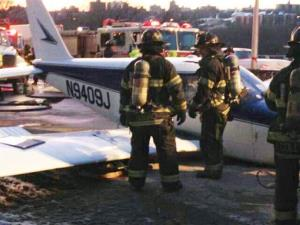 In this photo from the New York City Fire Department's Twitter account, firefighters stand near a light airplane that made an emergency landing on the Major Deegan Expressway.