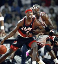 In this June 4, 1992, file photo, the Portland Trail Blazers' Cliff Robinson drives on the Chicago Bulls' Horace Grant. Robinson is among the stars reportedly set to play in a North Korea game.