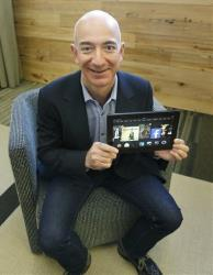 Jeff Bezos, CEO of Amazon, poses for a photo Tuesday, Sept. 24, 2013, with the 8.9-inch version of the new Amazon Kindle HDX.