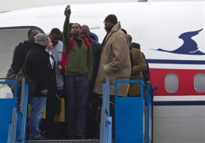 US basketball player Jerry Dupree, center, takes photos as he and fellow players including former NBA player Vin Baker, right, arrive at the international airport in Pyongyang today.