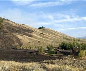 This Sept. 11, 2012 photo shows the burnt landscape from the Horsethief Canyon wildfire behind the home of James Anderson III just south of Jackson, Wyo.