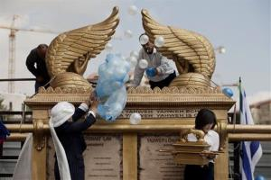A businesswoman from the Philippines releases balloons next to a model of the Ark of the Covenant in Jerusalem, Tuesday, Sept. 24, 2013.