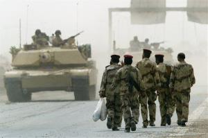 In this April 30, 2004, photo, Iraqi soldiers from the newly-formed Fallujah Brigade enter Fallujah as U.S. Marines, left, pull out from the town.