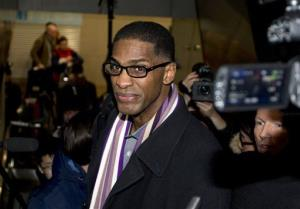 Former NBA basketball star Charles Smith is mobbed by journalists on an escalator upon arrival at the Beijing Capital International Airport in Beijing from North Korea, Friday, Jan. 10, 2014.