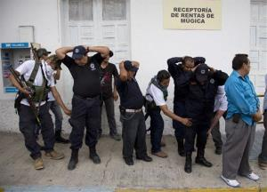 Vigilantes disarm municipal policemen during an operation to flush out alleged members of the Knights Templar drug cartel from the town of Nueva Italia, Mexico, Sunday, Jan. 12, 2014.