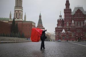 A Communist supporter carries red flags at Moscow's Red Square.