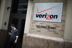 A man checks his cell phone during a smoke break outside the Verizon headquarters in lower Manhattan, Thursday, June 6, 2013.