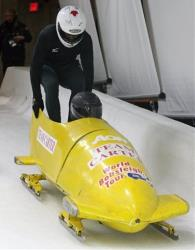 Jamaica two-man bobsled team brakeman Marvin Dixon jumps into their rented sled as Hannukkah Wallace pilots during the FIBT International training week in Whistler, British Columbia, on Nov. 2, 2009.