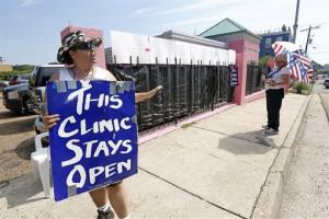 In this Aug. 15, 2013 photograph, an abortion rights supporter, left, argues with an abortion opponent, right, outside the Jackson Women's Health Organization clinic in Jackson, Miss.