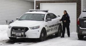 A police officer is seen outside a home in Mundelein, Ill., Wednesday, where an 11-year-old girl was stabbed to death on Tuesday.