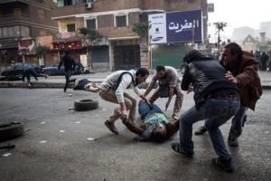 A mortally wounded supporter of Egypt's ousted Islamist president is evacuated as another wounded protester lies in the street during clashes with security forces in the Mohandiseen district of Cairo.
