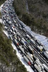 This aerial photo, traffic is snarled along the I-285 perimeter north of the metro area after a winter snow storm Wednesday, Jan. 29, 2014, in Atlanta.