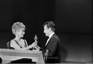 In this April 9, 1962 file picture, Joan Crawford presents an Oscar to Maximilian Schell on the stage at Santa Monica, Calif., April 9, 1962.